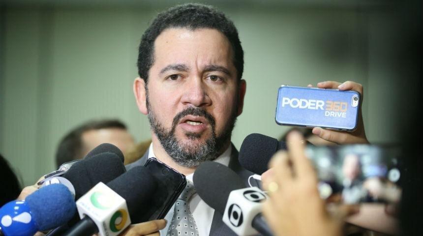 Ministro Dyogo Oliveira entre vários microfones durante entrevista coletiva