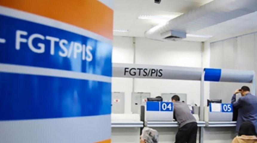 Foto da placa do PIS/Pasep com uma agência da Caixa Econômica ao fundo