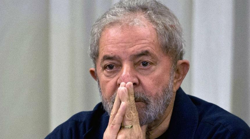 Ex-presidente Lula com as duas mãos em frente ao rosto, em sinal de desolação