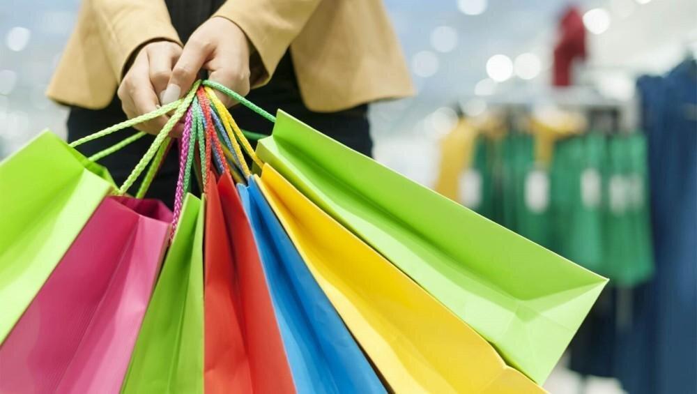 Parte do corpo de uma mulher com várias sacolas de compras