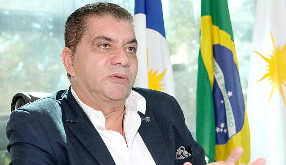 Carlos Amastha em frente a bandeiras de Palmas, Brasil e Tocantins