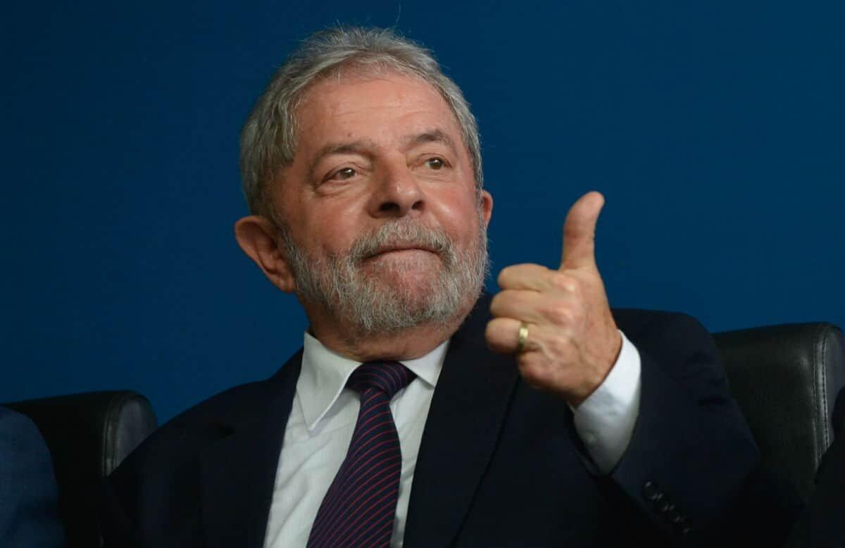 Lula, de terno, faz sinal de positivo