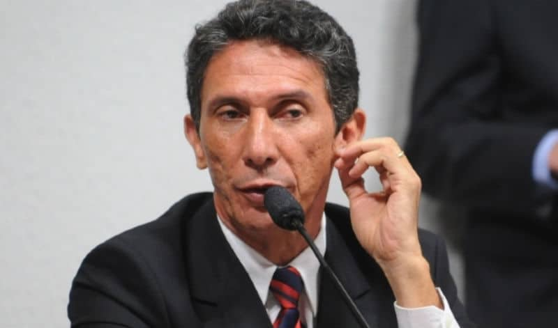 Ex-prefeito de Palmas Raul Filho à mesa leva a mão à orelha