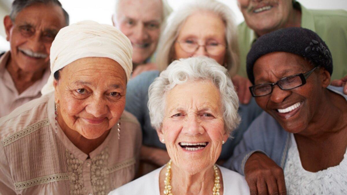 Várias idosas e alguns idosos sorriem