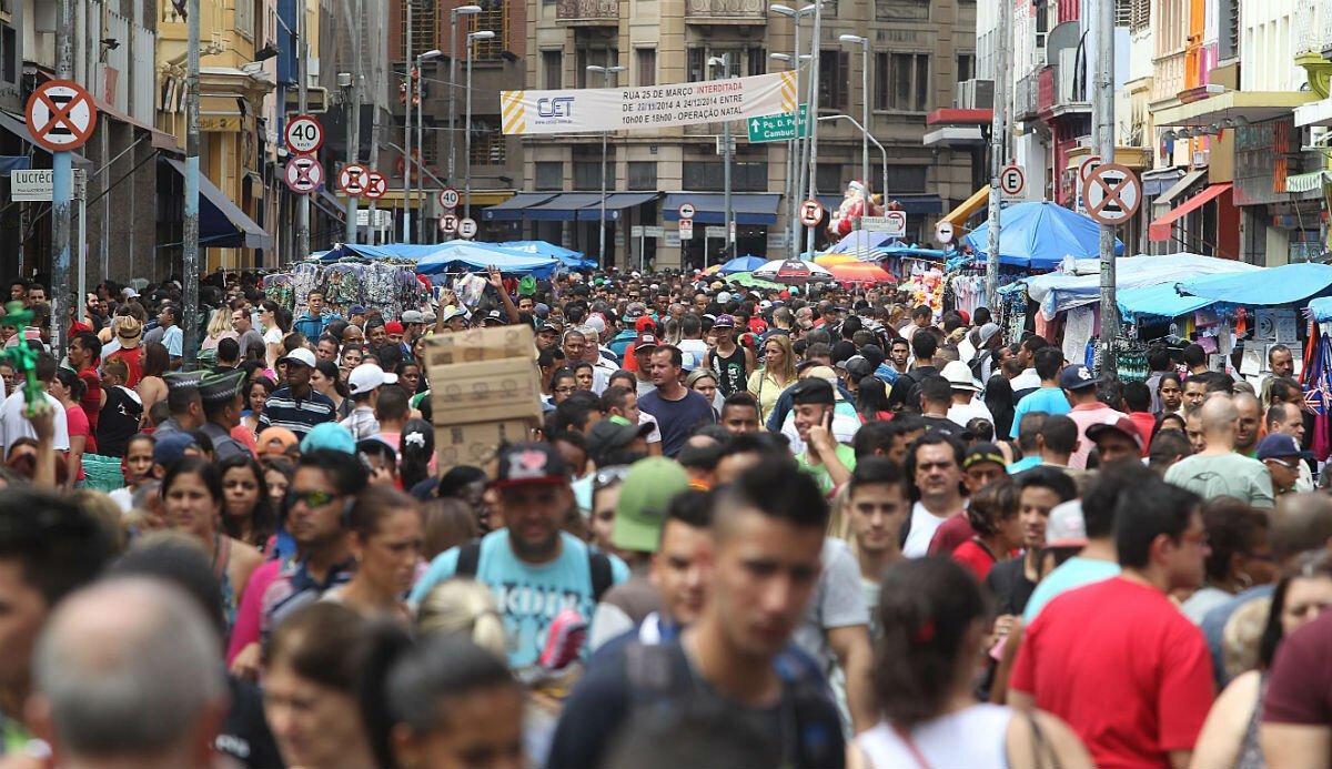 Muitas pessoas caminhando por uma rua estreita