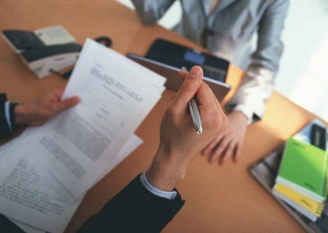Imagem parcial de uma pessoa, segurando a caneta em uma mão e um papel na outra, com uma pessoa à sua frente