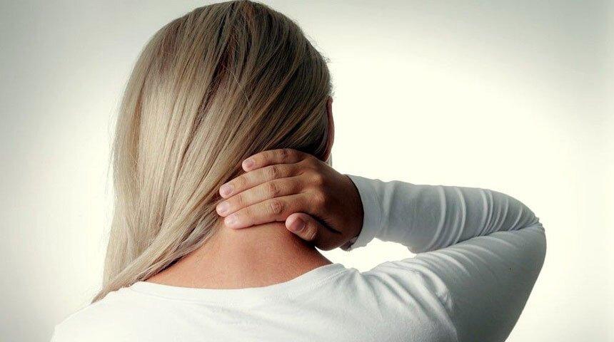Mulher loira, vista de costas, com a mão atrás do pescoço