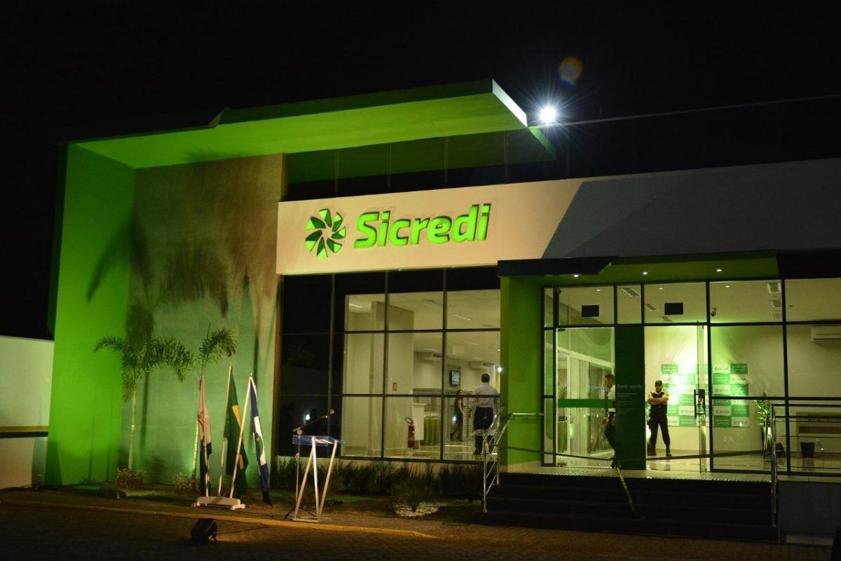 Agência do Sicredi à noite, destacada por iluminação verde