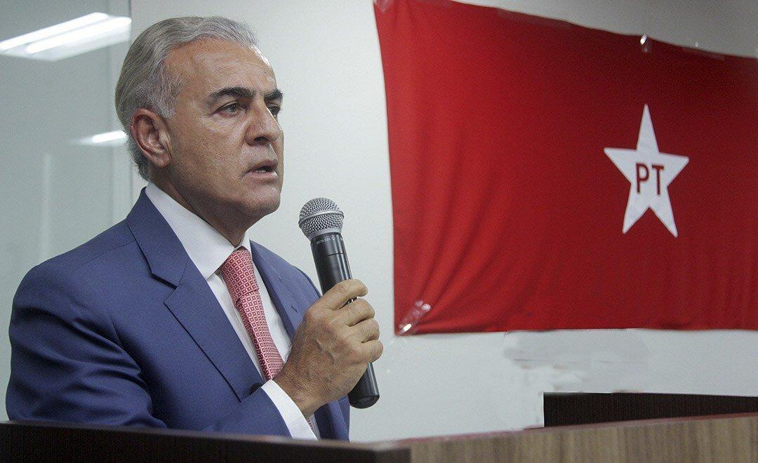 Paulo Mourão ao microfone, ao lado de bandeira do PT