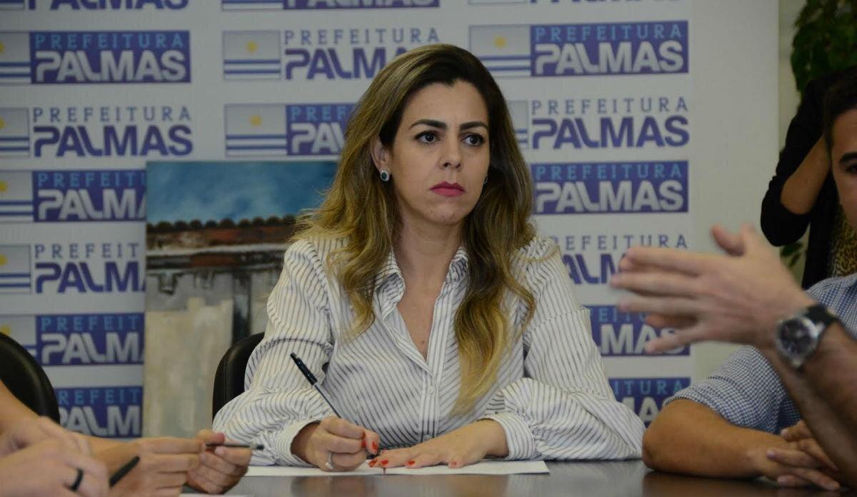 Prefeita Cinthia Ribeiro com a caneta posicionada sobre papel como se fosse escrever