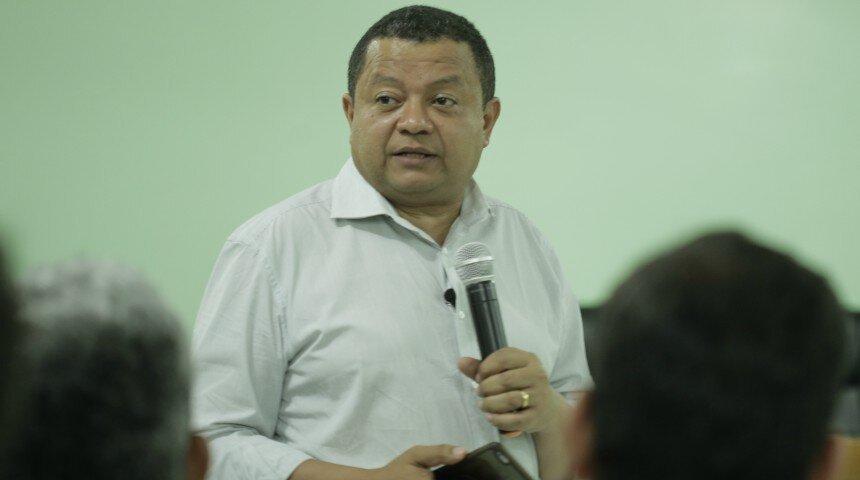 Candidato Márlon Reis em pé ao microfone, à frente de uma plateia
