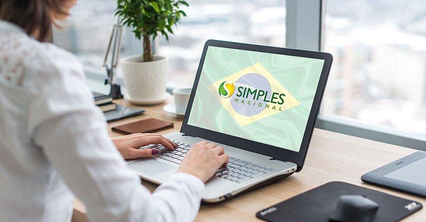 Uma pessoa digita num computador com os dizeres e logo do Simples Nacional na tela