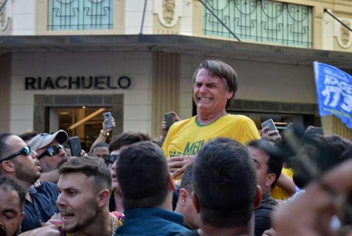 Jair Bolsonaro logo após ser esfaqueado faz cara de dor sobre o ombro de aliado