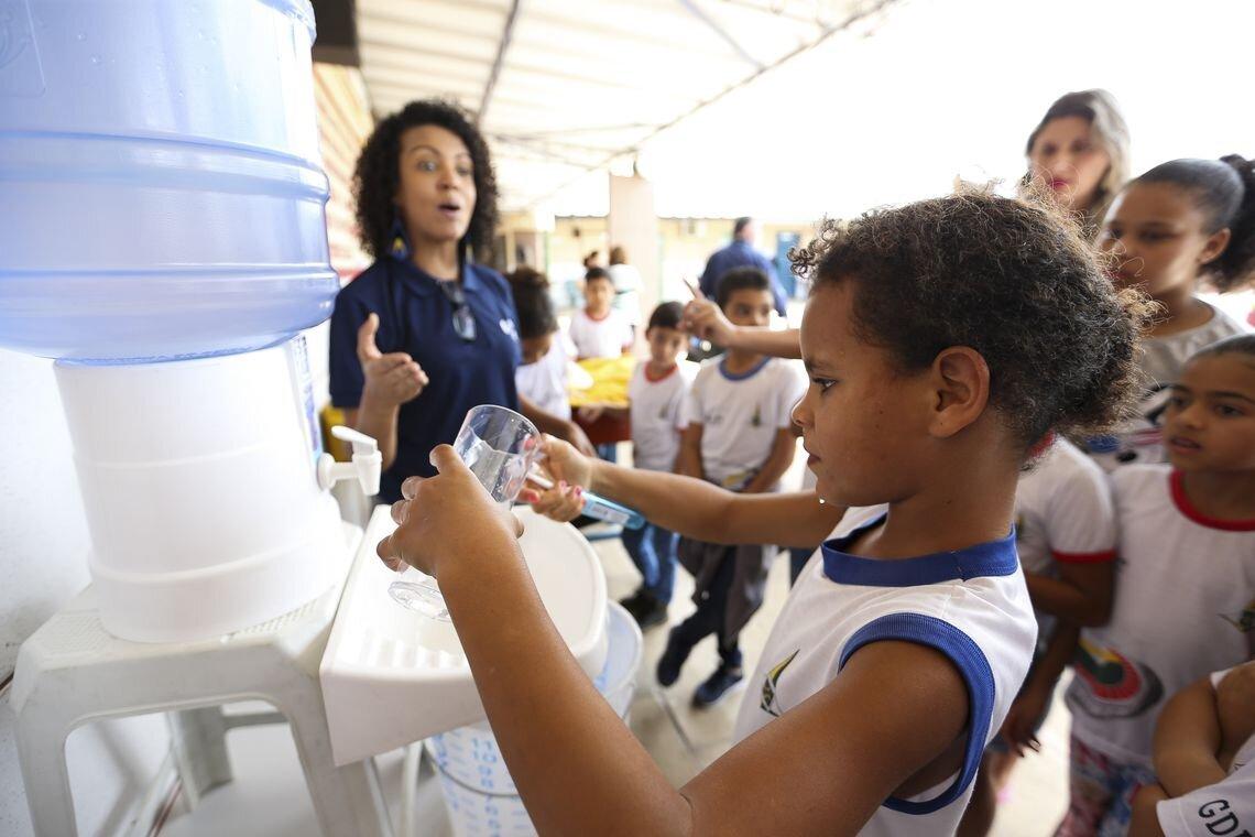 Criança retira água do bebedouro e, ao fundo, a professora e colegas de classe